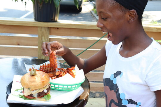 Happy black girl eating burger and sweet potato waffle fries while sitting at table on city street