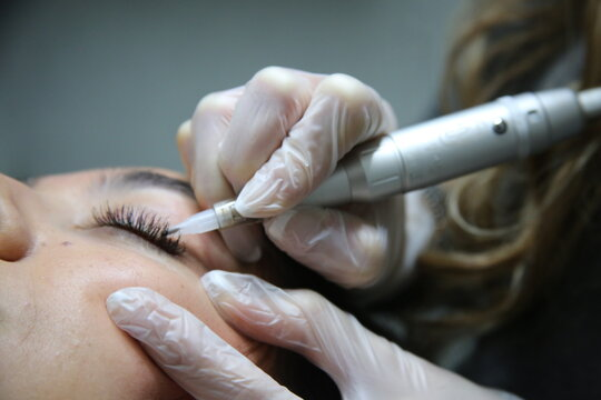 woman lying on couch at beauty salon with closed eyes and enjoying when cosmetologist making eyeliner and  eyebrow  permanent make up. Professional wearing black gloves and holding speciality tool.