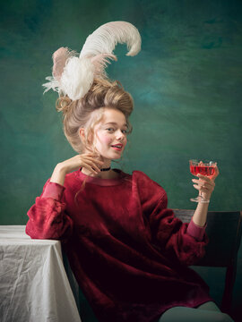 Alcohol cocktail time. Young woman as Marie Antoinette on dark green background. Retro style, comparison of eras concept. Beautiful female model like classic historical character, old-fashioned.