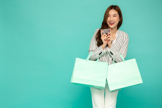 Portrait of smiling asian women holding credit card and green shopping bag isolated over green background, Happy feeling of shopper concept