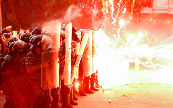 Fireworks are set off in front of police officers during anti-government protests that have been ignited by a massive explosion in Beirut