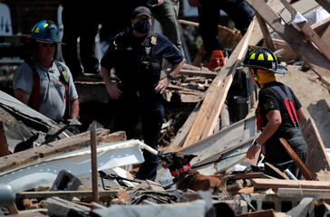 A fire fighter and a rescue dog look for survivors at the scene of an explosion in a residential area of Baltimore