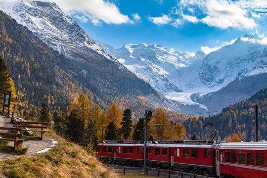 Stunning view of red Rhaetian train running under the Morteratsch Glacier in autumn with blue sky cloud, on sightseeing railway line Bernina Express, Canon of Grisons, Switzerland