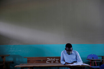 A pupil wearing a face mask to prevent the spread of the coronavirus disease (COVID-19), reads as he sits at a schoolroom waiting for the start of the lessons during the first day of school after holidays, in Port au Prince