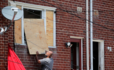 A man covers a damaged window with plywood, near the scene of an explosion in a residential area of Baltimore