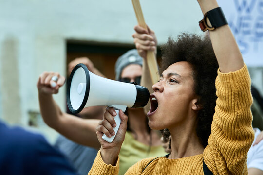 African American woman with raised fist shouting through megaphone on anti-racism protest.