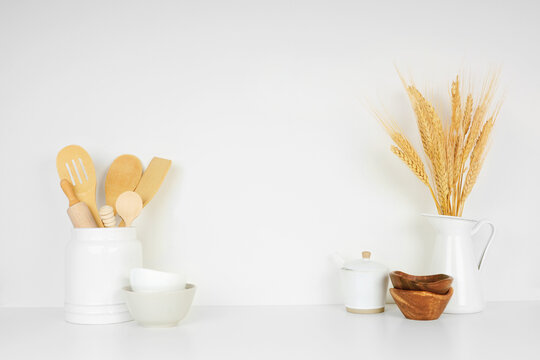 Kitchenware and utensils on a white shelf or counter against a white wall background with copy space. Home kitchen cooking decor.