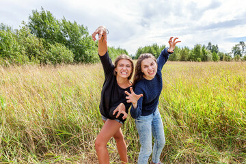 Summer holidays vacation happy people concept. Group of two girl friends dancing hugging and having fun together in nature outdoors. Lovely moments best friend.