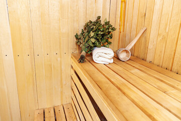 Interior details Finnish sauna steam room with traditional sauna accessories basin birch broom scoop felt hat towel. Traditional old Russian bathhouse SPA Concept. Relax country village bath concept.