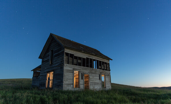 View of abandoned house on farm at dusk