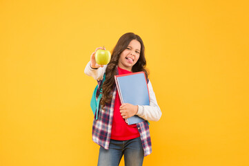 Apple is out of season now. Little child make face holding apple and books yellow background. Sour...