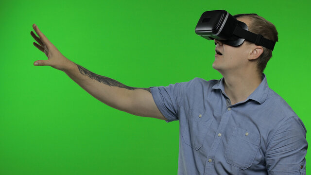 Man using VR app helmet to play simulation game, drawing. Guy watching virtual reality 3d video