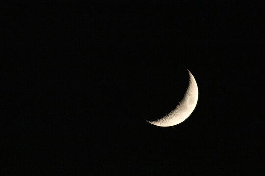 Sliver of moon in dark night sky
