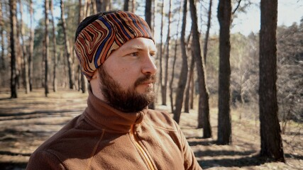 Foto auf Leinwand Braun Active male sporty guy portrait hiking outdoors. Young male tourist with a beard and bandage, kerchief on his head wearing a backpack outdoors Caucasian
