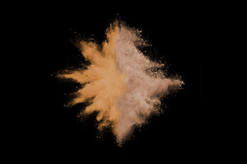 Gold sand explosion isolated on black background.