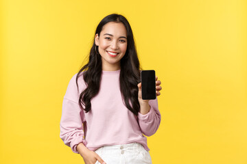 People emotions, lifestyle leisure and beauty concept. Smiling asian woman 20s, showing smartphone...