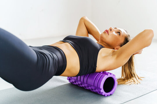 Adult sporty woman doing fascia exercise on the floor - Caucasian female using foam massage roller - tool for back tension and muscle pain release - physical therapy and training stretch concept
