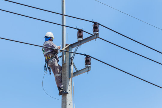 Electricians Wiring Cable repair services,worker in crane truck bucket fixes high voltage power transmission line,setting up the power line wire on electric power pole.