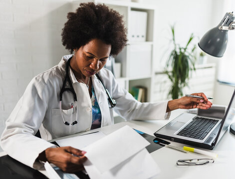 Woman doctor with stethoscope looking at medical papers at her office working hard