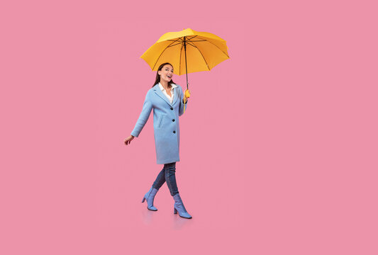 Portrait of excited young woman walking with umbrella