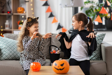 halloween, holiday and childhood concept - smiling little girls in costumes with candies at home