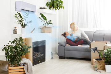 Fototapeta air conditioning in living room with happy family moving to new apartment