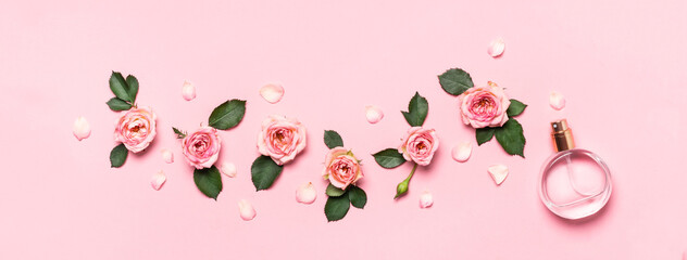 Women's perfume bottle and roses flowers buds and petals. Minimal beauty banner