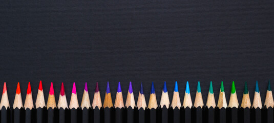 Creative minimal banner. Colored pencil set arranged in line on black background