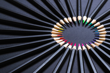 Colored pencil set arranged in circle on black background. Stationery minimal round frame