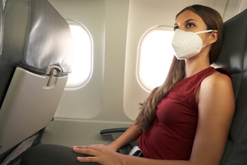 Fly Safe. Young business woman wearing KN95 FFP2 mask is traveling on airplane. New normal travel after coronavirus pandemic.