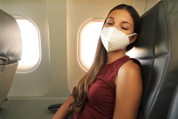 Brazilian woman with protective face mask sleeping relaxed on airplane flight during pandemic coronavirus