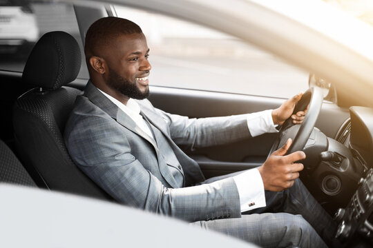 Cheerful african american businessman driving to work