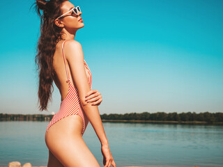 Young beautiful sexy hipster woman in sunglasses posing  on sea background.Trendy woman in summer...