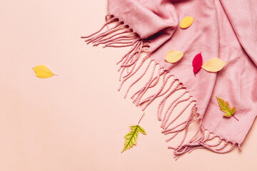 Pink cozy scarf with tassels and scattered leaves on pastel background. Hello autumn concept