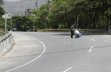 A man wearing a protective mask transports plastic containers across a highway to be filled with water that accumulated at a stalled tunnel construction project near El Avila mountain that borders the city of Caracas