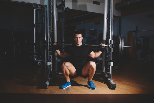 Young professional bodybuilder working out doing squats with barbell