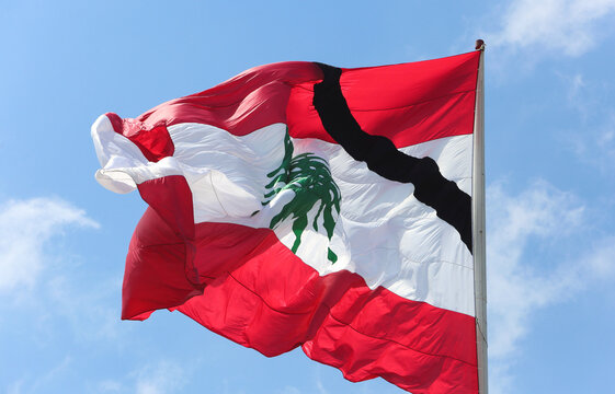 A Lebanese national flag bearing a black line, as a symbol of mourning, is seen after a massive explosion in Beirut