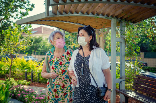 Companion or assistant and elderly lady chatting casually as they pass a wooden pergola in a park. Both are wearing protective masks during coronavirus.
