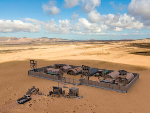 Military compound in the middle east, aerial view of a military base. Guard towers and reinforced concrete fence. Defense of terrorist attacks, 3d render