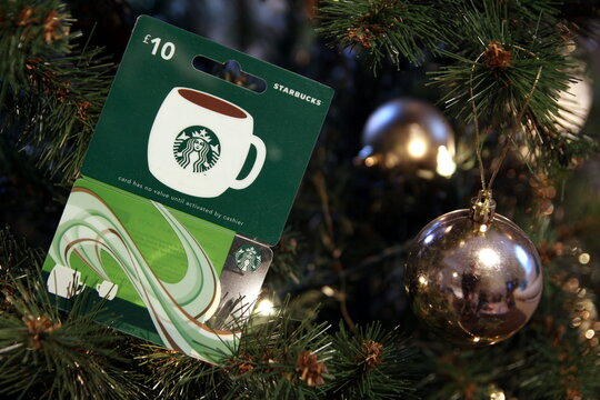 Camberley, UK - 31 Dec 2016: British Starbucks £10 gift card or voucher, nestled among the branches of a Christmas tree