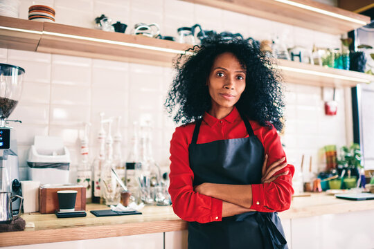 Portrait of experienced african american barista with crossed hands looking at camera.Professional dark skinned female waitress dressed in black apron standing on working place in own cafeteria