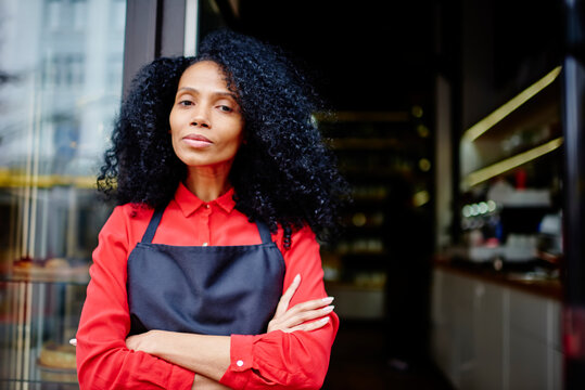 Half length portrait of professional african american barista with curly hair looking at camera while standing outdoors at entrance to coffee shop.Confident dark skinned female owner of cafe
