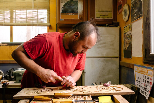 Wood carver using metal chisel while creating ornaments on plank working in workshop