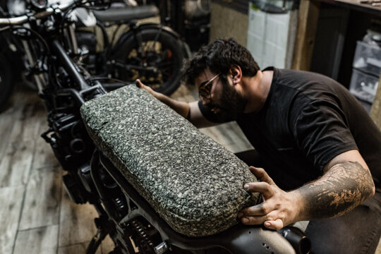 Tattooed male biker standing in shabby garage and working on seat while fixing motorbike