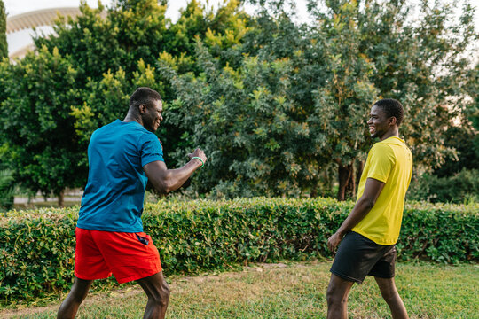 Side view of athletic black friends wearing colorful clothes doing boxing exercises in the park