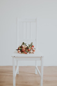 Vintage bridal flower bouquet placed on a white wooden chair in an empty room with white walls