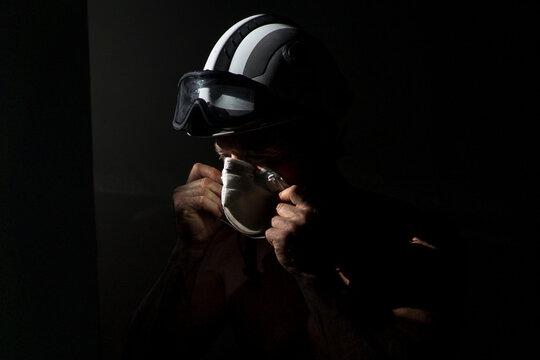Mature fireman wearing hardhat and protective respirator during coronavirus pandemic on black background in dark studio