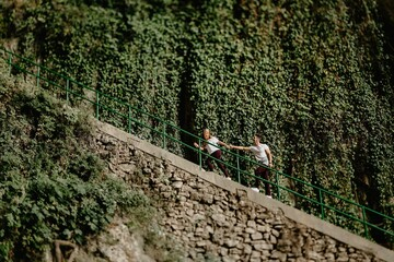 Side view low angle of young man following cheerful girlfriend while walking up stairs near green shrubs during exciting journey in nature