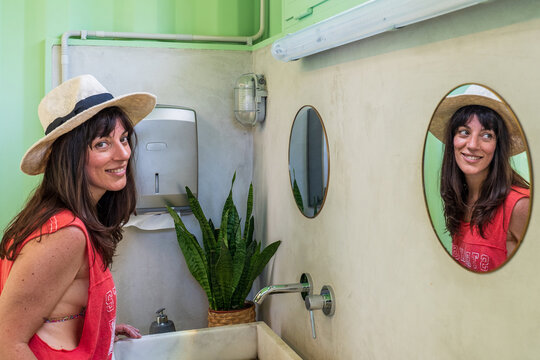 Side view content female in beachwear and hat standing in creative public restroom with green walls and looking in mirror near sink