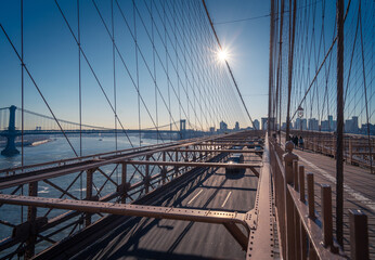 Cars driving on famous Brooklyn bridge over river in sunny afternoon in New York City